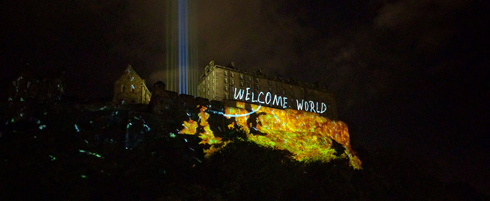 A photo of Edinburgh International Festival's Deep Time event, showing Edinburgh Castle lit up at night by a projection of the words 'Welcome World'