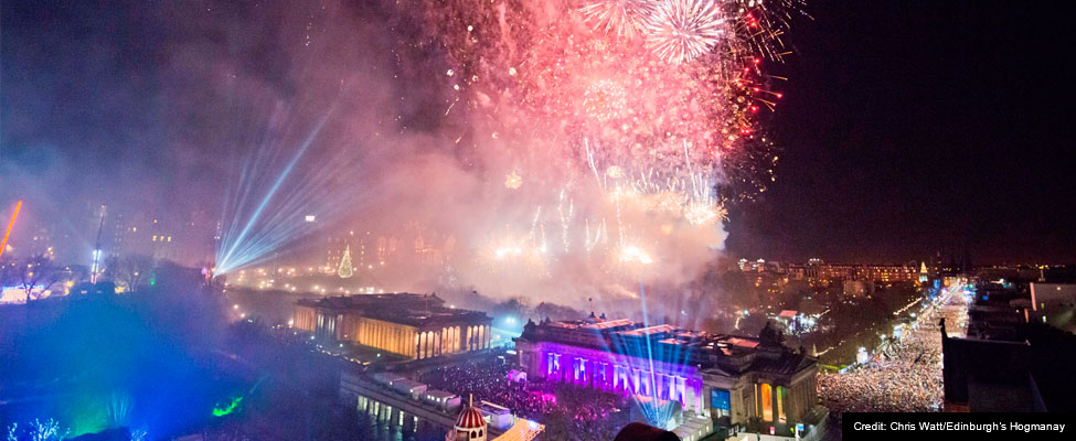 A photo of Edinburgh during the Hogmanay midnight moment with huge crowds on the streets and spectacular fireworks bursting over the city centre